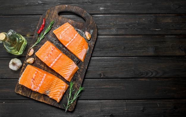 Filé de salmão cru com alho e ervas. em uma madeira.