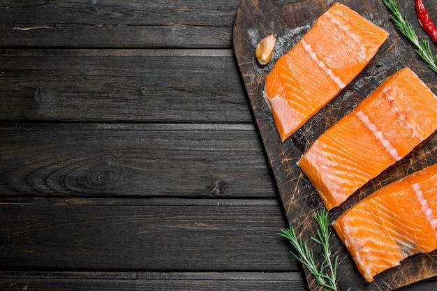 Filé de salmão cru com alho e ervas na mesa de madeira.