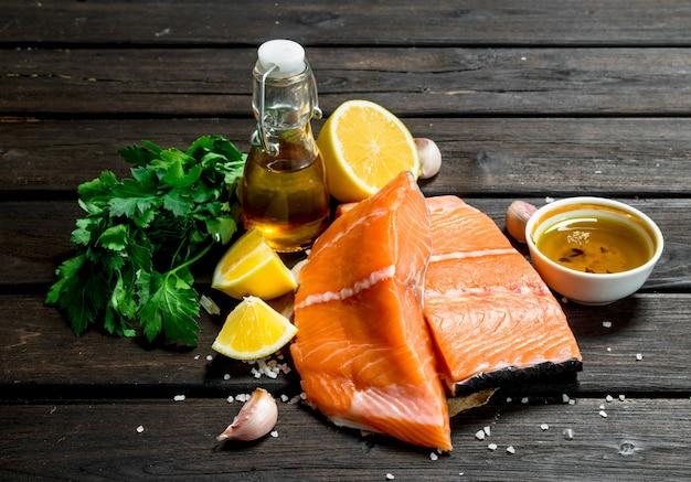 Filé de salmão cru com legumes, especiarias e azeite na mesa de madeira.