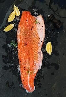 Filé de salmão cru com limão e alecrim no gelo lascado sobre pedra escura
