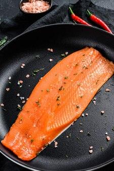 Filé de salmão cru com sal e pimenta em uma panela