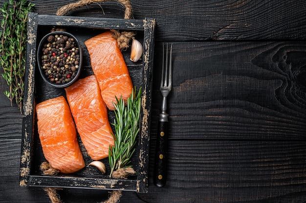 Filé de salmão cru, filé de peixe em tabuleiro de madeira com tomilho e alecrim. fundo de madeira preto. vista do topo. copie o espaço.