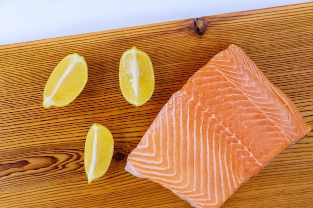 Filé de salmão cru fresco com tábua de madeira sobre fundo branco