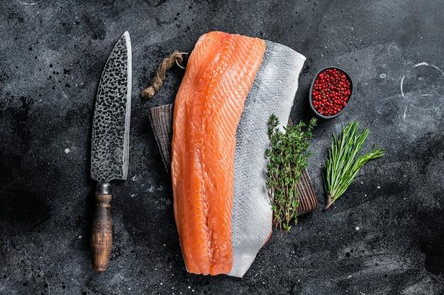 Filé de salmão cru fresco na tábua com faca. fundo preto. vista do topo.