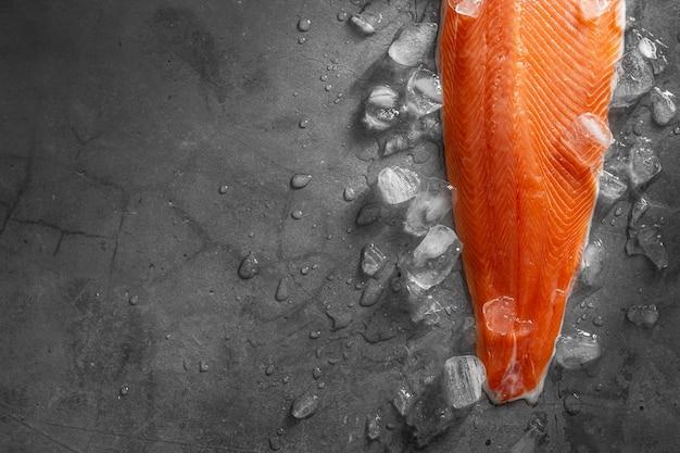 Filé de salmão cru fresco no gelo sobre fundo escuro de pedra. layout criativo feito de peixes, vista superior, camada plana