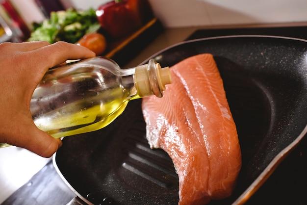 Filé de salmão cru na panela, cozinhar derramando azeite sobre ele para cozinhá-lo.