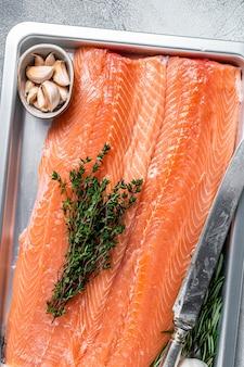Filé de salmão do mar cru cru em uma bandeja de cozinha com ervas. fundo branco. vista do topo.