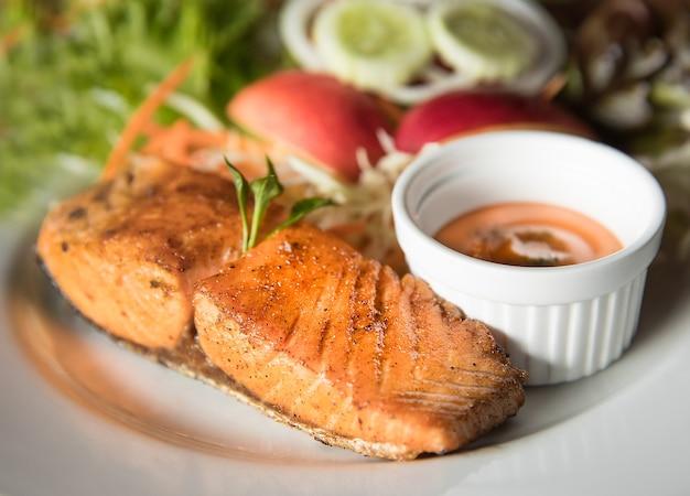 Filé de salmão em prato branco com molho e legumes no fundo