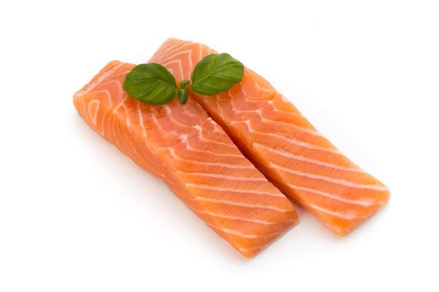 Filé de salmão fresco com manjericão no fundo branco.