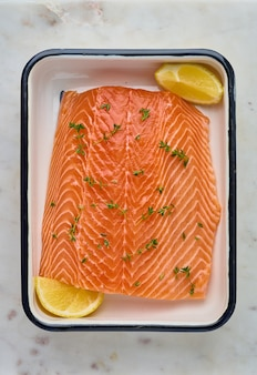 Filé de salmão fresco cru de corcunda com alecrim e rodelas de limão na vertical acima