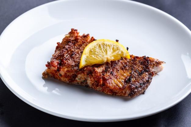 Filé de salmão fresco e grelhado com uma fatia de limão suculento em um prato branco
