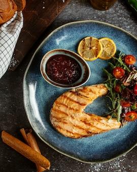 Filé de salmão frito com legumes e rodelas de limão