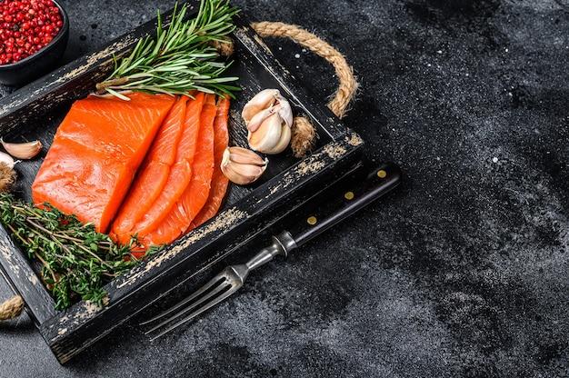 Filé de salmão fumado às rodelas em tabuleiro de madeira com ervas aromáticas. fundo preto. vista do topo. copie o espaço.