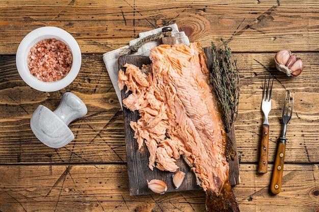 Filé de salmão fumado quente em uma placa de madeira. fundo de madeira. vista do topo.