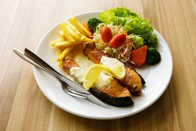 Filé de salmão grelhado com batata frita e salada de legumes no disco branco