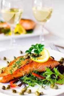 Filé de salmão grelhado com legumes e um copo de vinho branco.