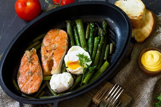 Filé de salmão grelhado com ovo escalfado de aspargos em uma frigideira comida saudável vista superior