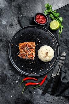 Filé de salmão japonês teriyaki grelhado, envidraçado com molho delicioso com um prato de arroz. superfície preta. vista do topo