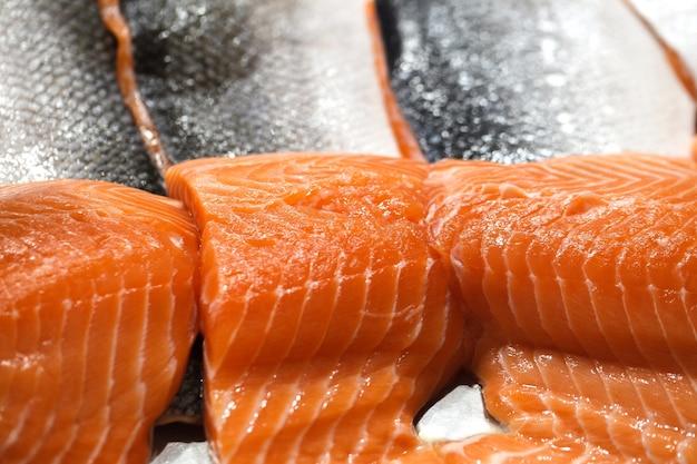 Filé de salmão no gelo, pedaços crus frescos e refrigerados, na peixaria.