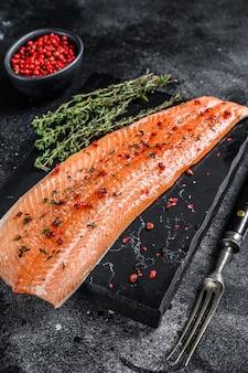 Filé de salmão ou truta de peixe marinho com sal e pimenta rosa fundo de madeira preta vista superior