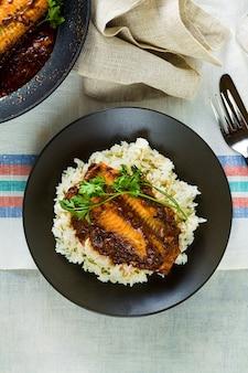 Filé de salmão rosa ao molho de tomate e coco em uma frigideira antiaderente com salsa sobre uma mesa com toalha de linho. comida familiar saudável com arroz basmati