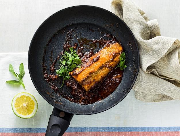 Filé de salmão rosa ao molho de tomate e coco em uma frigideira antiaderente com salsa sobre uma mesa com toalha de linho. comida familiar saudavel