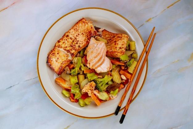 Filé de salmão rosa com legumes salteados asiáticos. vista do topo.
