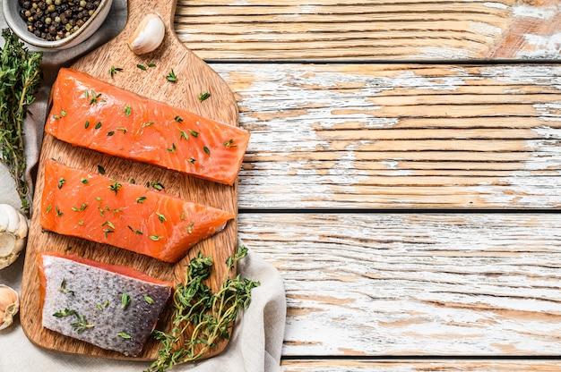 Filé de salmão salgado com tomilho em madeira branca. vista do topo. copie o espaço