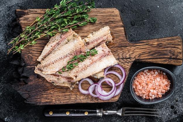 Filé de sardinha de peixe ao azeite em tábua de madeira