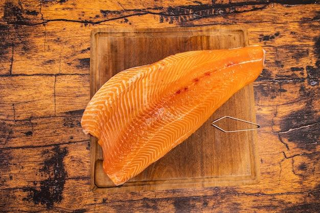 Filé grande de salmão cru em uma placa de madeira com um alicate de espinha de peixe