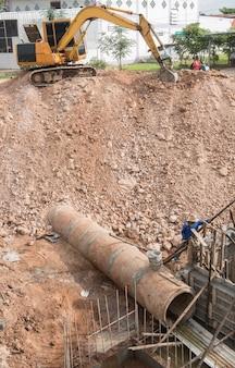 Fileira da tubulação de drenagem concreta sob a terra perto da retroescavadeira na área da construção.