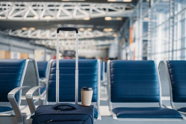Fileira de assentos e bagagem de mão no saguão do aeroporto