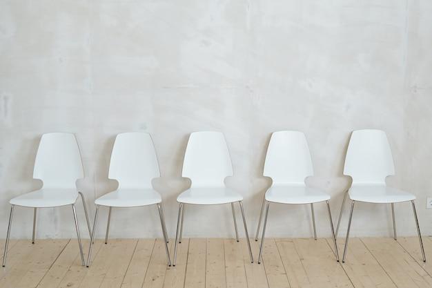 Fileira de cadeiras de plástico brancas com pernas de metal colocadas em parquet contra uma parede cinza