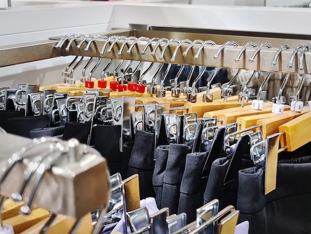 Fileira de calças pretas com cabides de pano em loja de roupas com foco seletivo