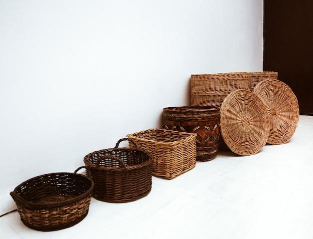 Fileira de cestos de palha de vime para armazenamento com alça e tampa no chão branco