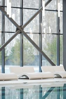 Fileira de espreguiçadeiras brancas ao longo de grandes janelas e piscina com água transparente dentro de um hotel moderno, spa ou centro de lazer