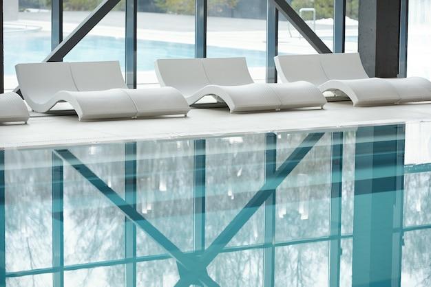 Fileira de espreguiçadeiras de plástico branco ao longo de grandes janelas e piscina com água transparente dentro de um moderno centro de spa