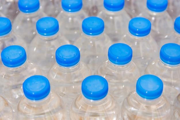 Fileira de garrafas de água. garrafas com tampas azuis para beber água