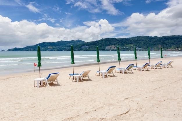 Fileira de guarda-sóis e cadeiras na praia em um dia ensolarado