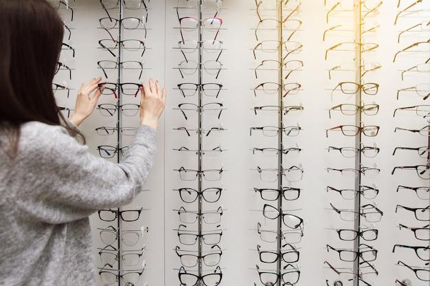 Fileira de óculos em um oculista. loja de óculos. fique com óculos na loja de ótica.