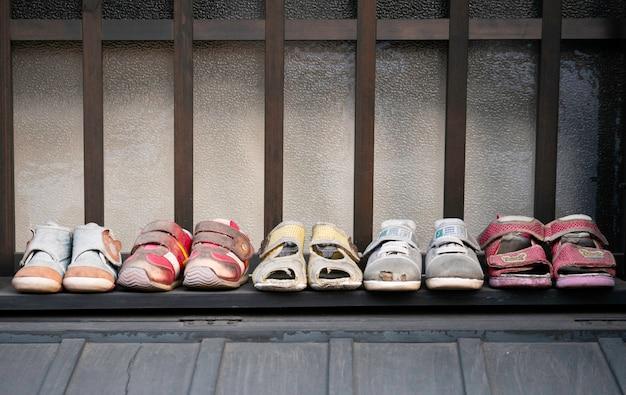 Fileira de sandálias usadas velhas da criança, deslizadores, sapatas das sapatilhas no assoalho.