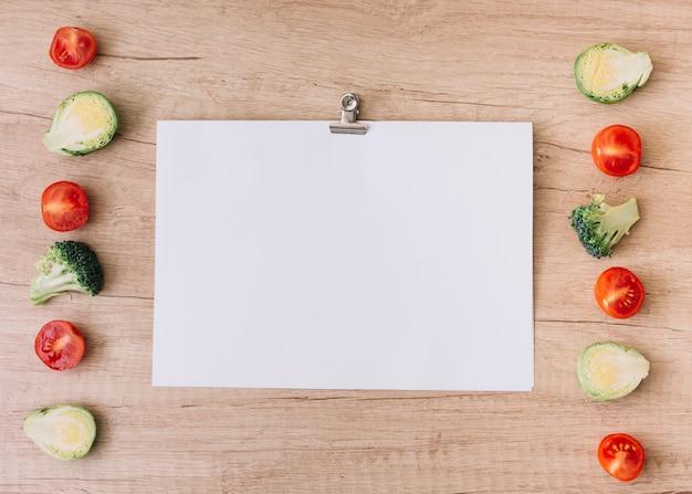 Fileira de tomates cereja; couve de bruxelas e brócolis perto do papel branco em branco com clipe de papel