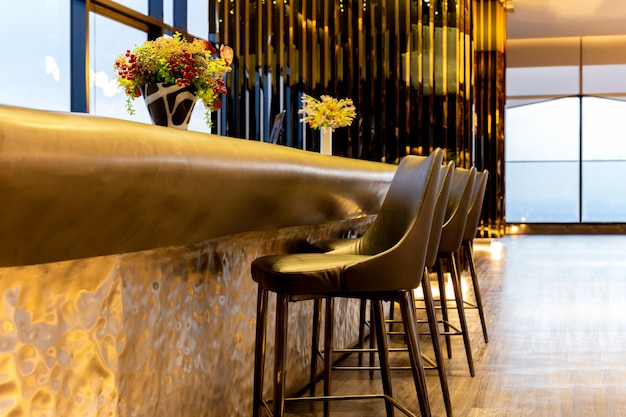 Fileira do design de interiores da cadeira moderna dos tamboretes do couro na sala de estar luxuosa.