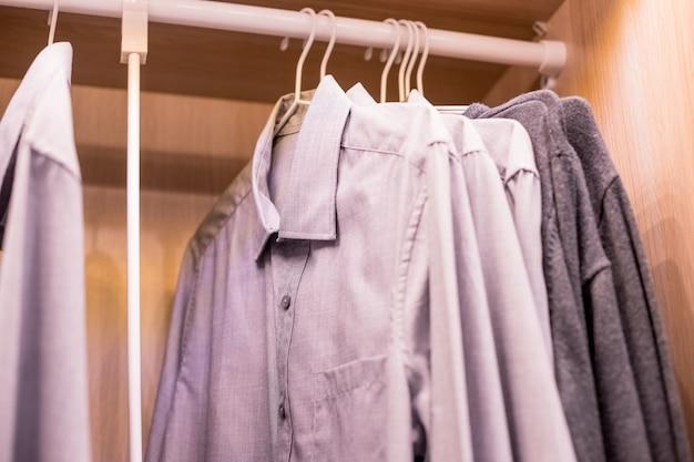 Fileira dos ternos dos homens que penduram no closet.buy e vendem, homem de negócio. armário do homem.
