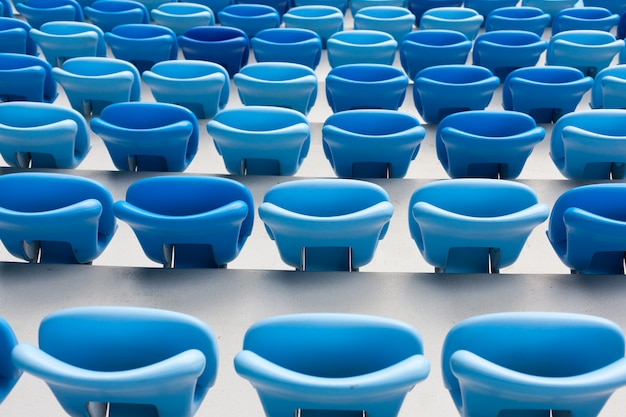 Fileiras de assentos azuis no estádio de futebol.