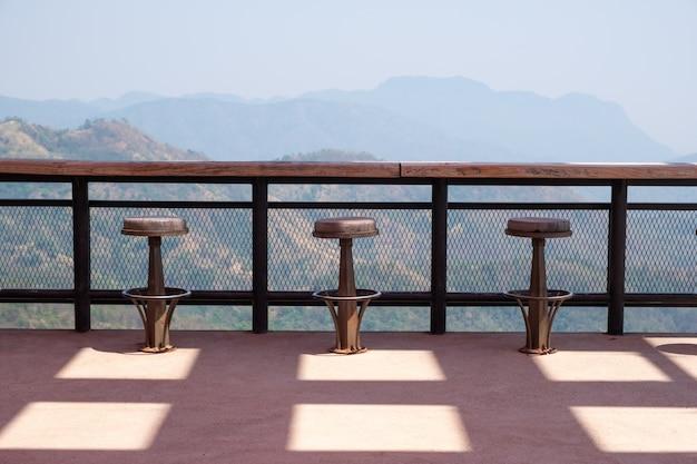 Fileiras de bancos de madeira e balcão no terraço ao ar livre