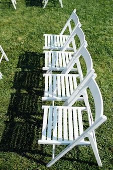 Fileiras de cadeiras dobráveis brancas no gramado