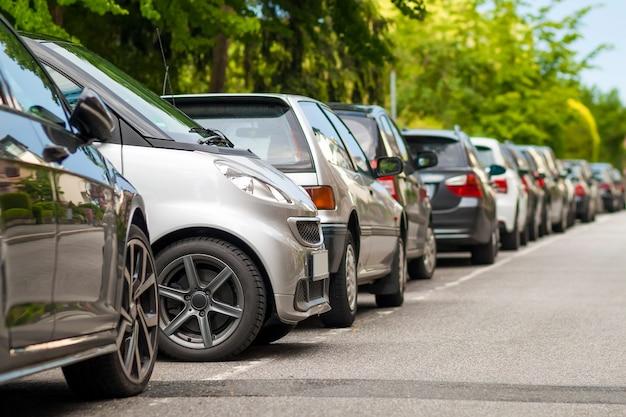 Fileiras de carros estacionados na beira da estrada em um bairro residencial. carro pequeno estacionado entre outros carros.