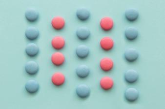 Fileiras de doces-de-rosa e azuis sobre fundo verde