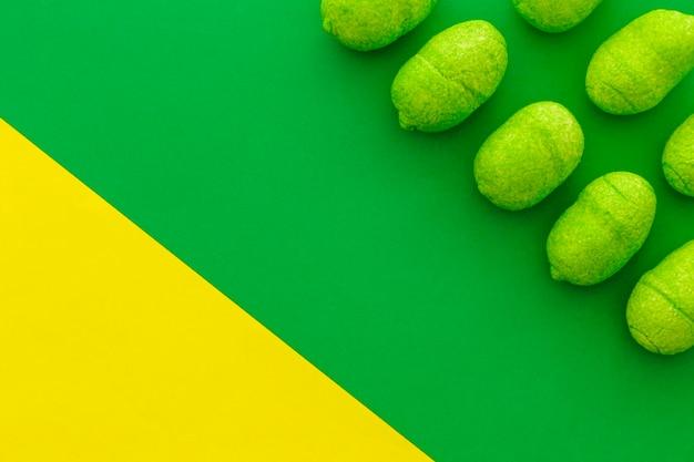Fileiras de doces doces em pano de fundo duplo verde e amarelo